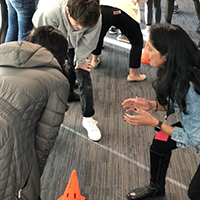 Three students gathered around a traffic cone in a thinking activity