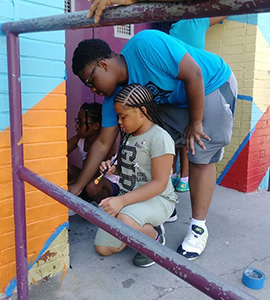 Students involved in Youthworks painting murals in Baltimore