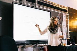 Photo of teacher pointing to large TV screen