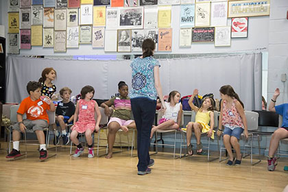 Loyola students leading a music class of children