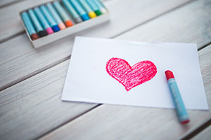 Paper with a red heart and crayons on a table
