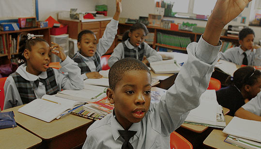 Students in the classroom raising their hands