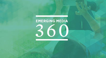 A student laying in a grassy field, using a mobile device. The text - Emerging Media 360 - is placed on the image