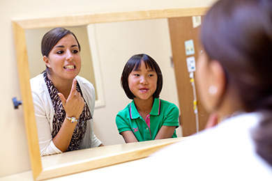Speech-language pathology student working with a child