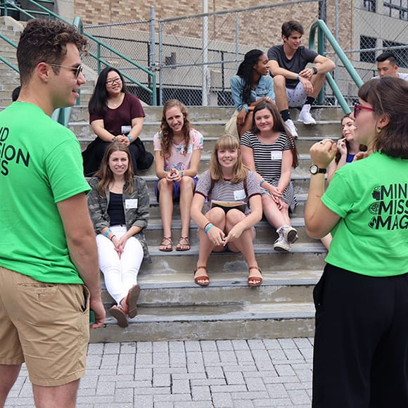 Two Evergreen students guiding a group of freshmen sitting on stairs outside