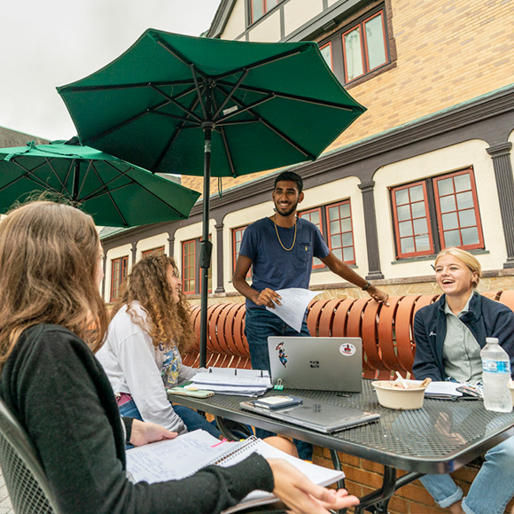 Students talking and smiling around an outdoor table