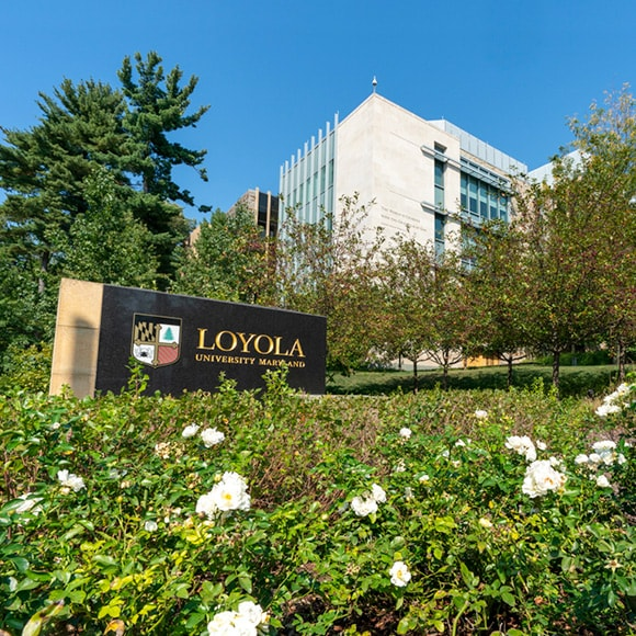 Flowers blooming in front of a Loyola sign and the Donnelly Science Center