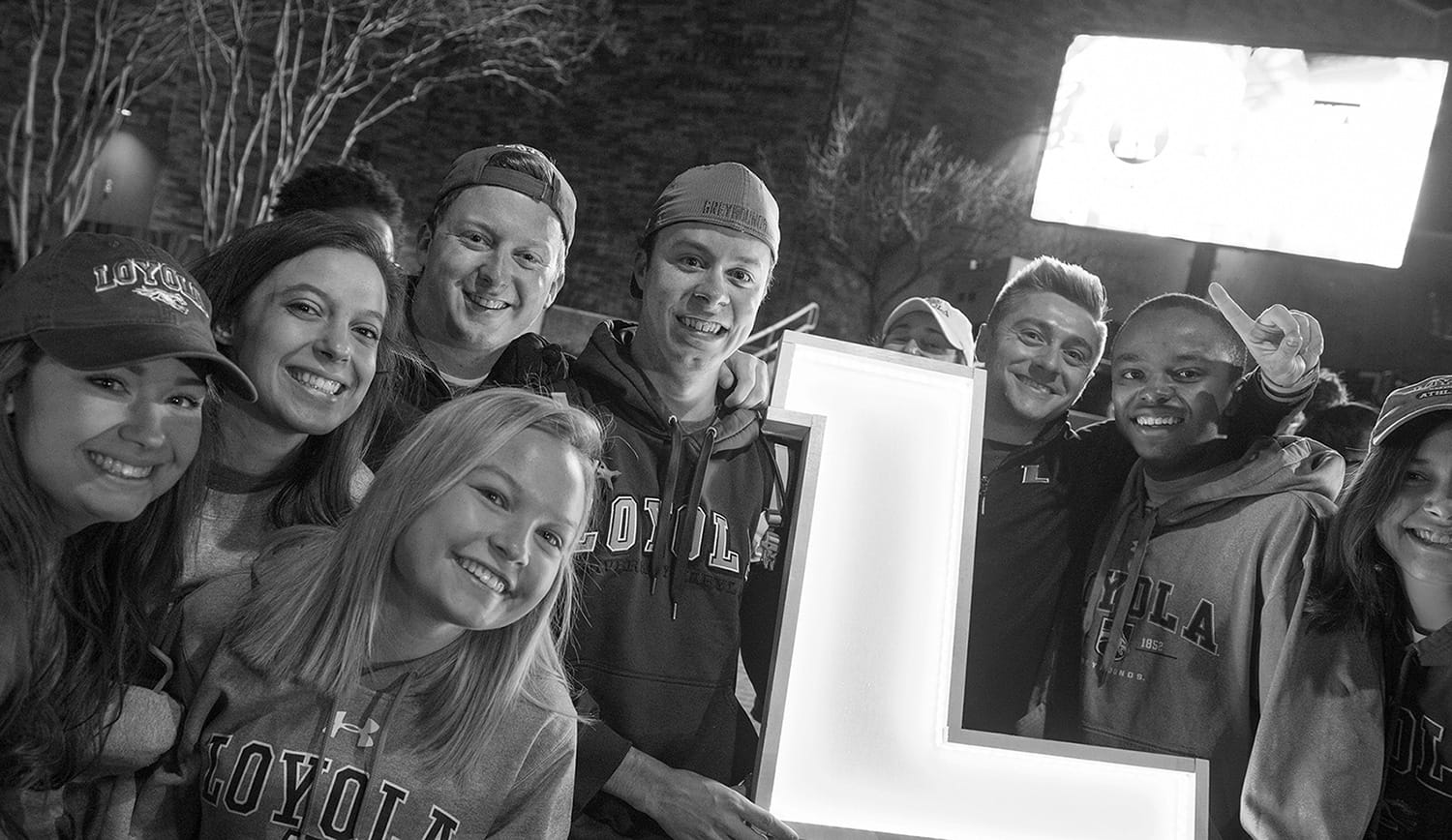 A group of students posing for the camera while holding a glowing L