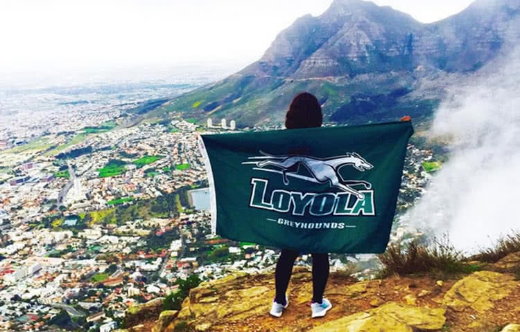 A student holding a Loyola flag while standing above a valley in a foreign country