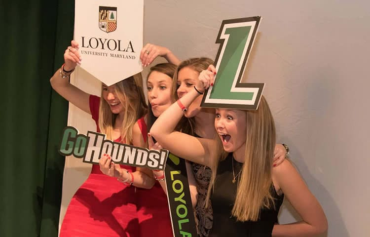 Several students holding up Loyola signs