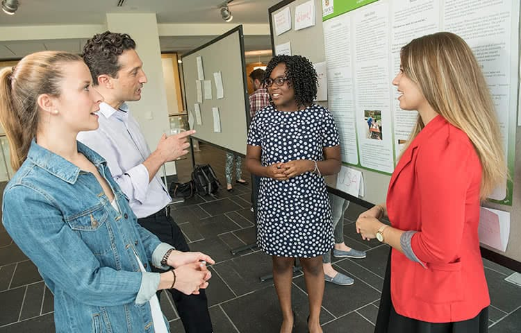 Students and a professor having a discussion at a poster session