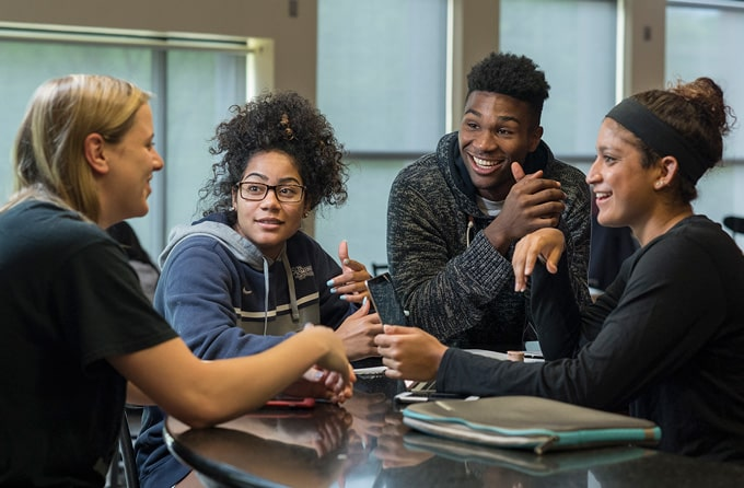 Group of students laugh together in a residence hall.
