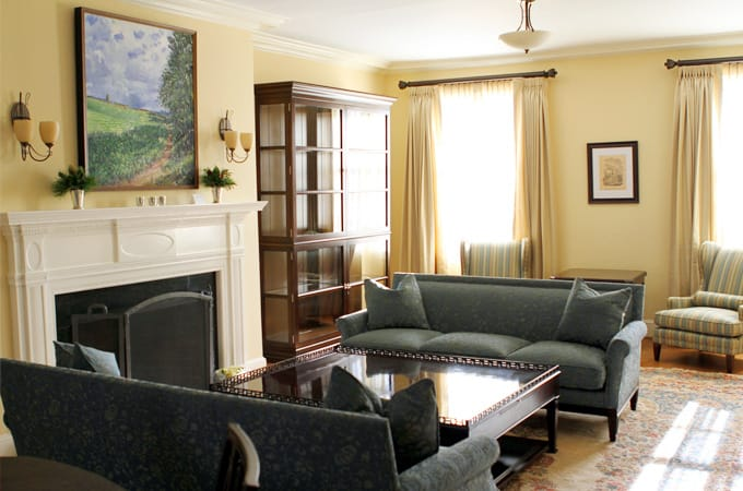 A tan room filled with blue couches, a fireplace, and other furniture. A painting of a field hangs on the wall.