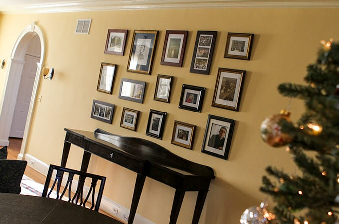 Loyola photos in picture frames hang on a tan wall, with a decorated Christmas tree in the foreground
