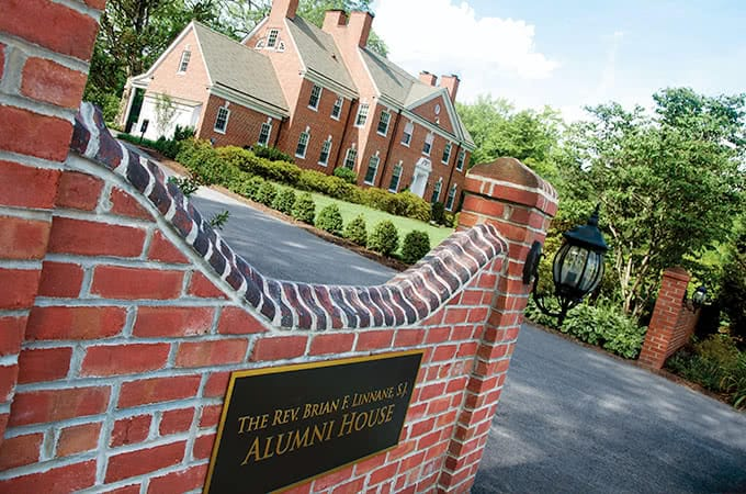 A red brick wall with a sign reading The Rev. Brian F. Linnane Alumni House, and a red-bricked building in the background
