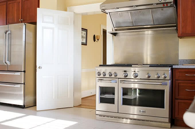 A kitchen with a stainless steel stovetop, oven, and refrigerator