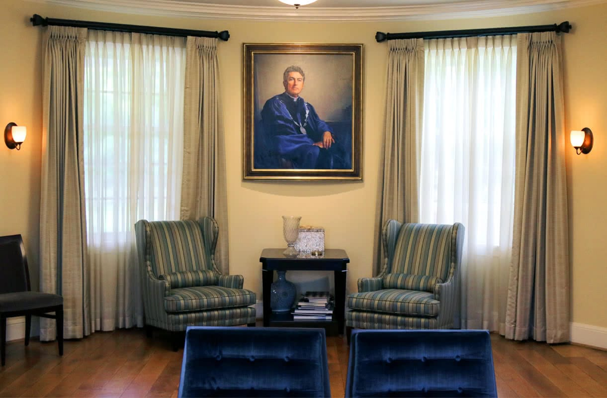 A painting of Brian Linnane hung on a tan wall, flanked by two windows