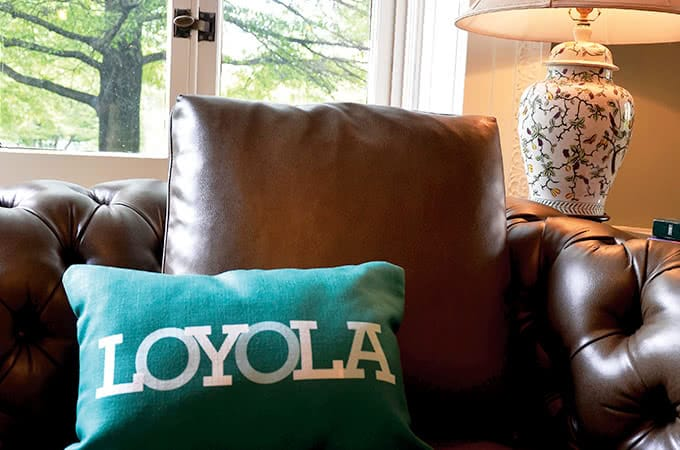 Close-up of a green Loyola pillow sitting atop a brown leather couch