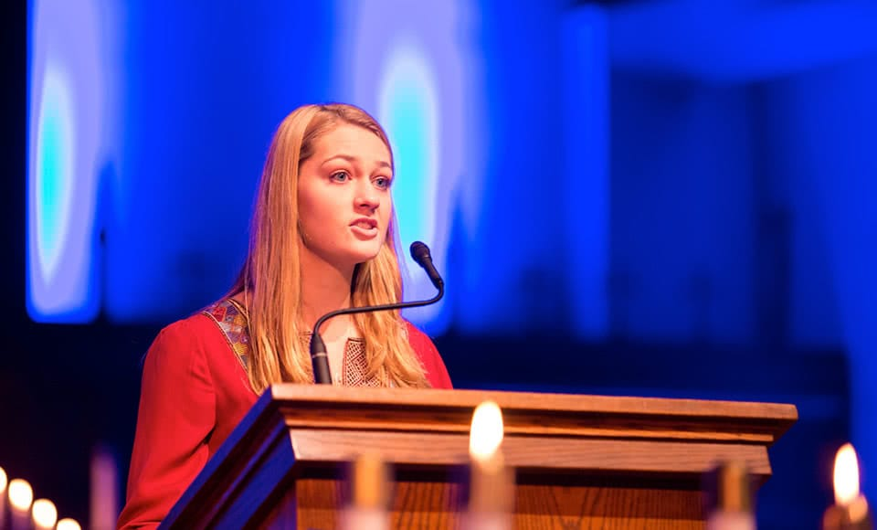 Female student speaking at pulpit