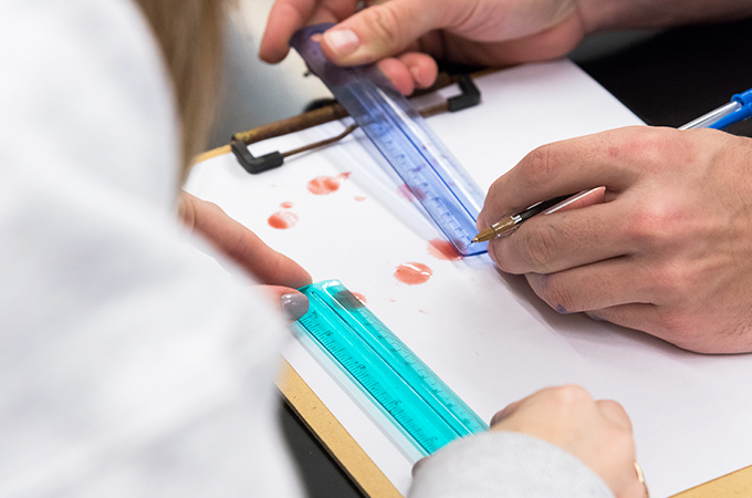 Students measure drops of blood for a lab assignment.