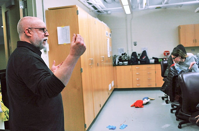 A faculty member explains a mock crime scene.