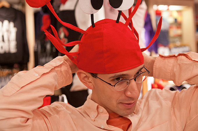 A student with glasses tries on a red crab hat