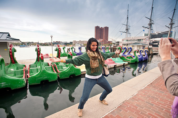 A student poses in front of dragon paddle-boats parked in the harbor