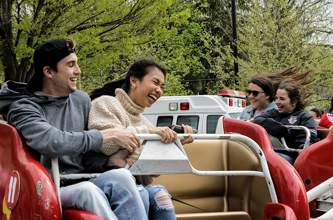 Students laughing while on a ride that spins