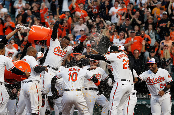 Baltimore Orioles baseball players celebrate at home plate in front of a cheering crowd