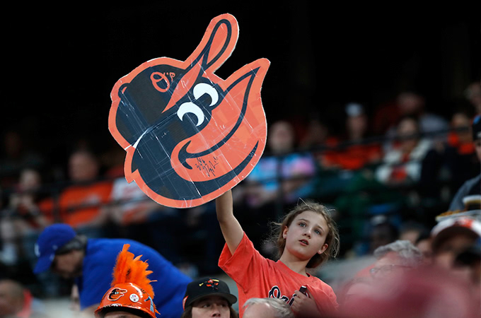 A young girl holds up an Orioles sign in the crowd during a baseball game