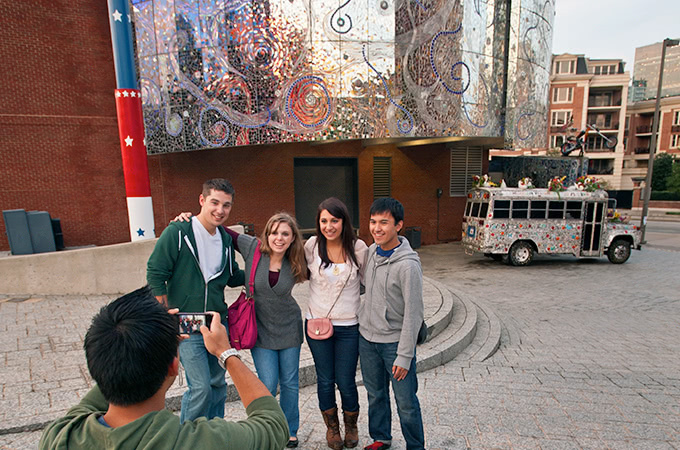 Students posing for a picture in front of the metallic and tile facade of The American Visionary Arts Museum