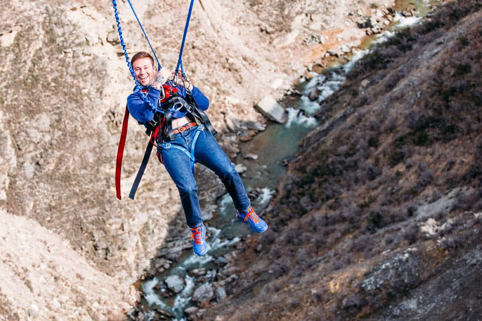 A student smiling while bungee jumping in New Zealand
