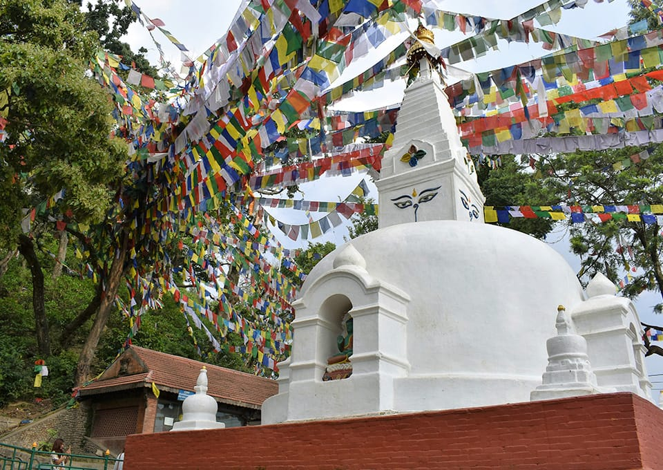 A small, white, stupa with colorful prayer flags hanging above