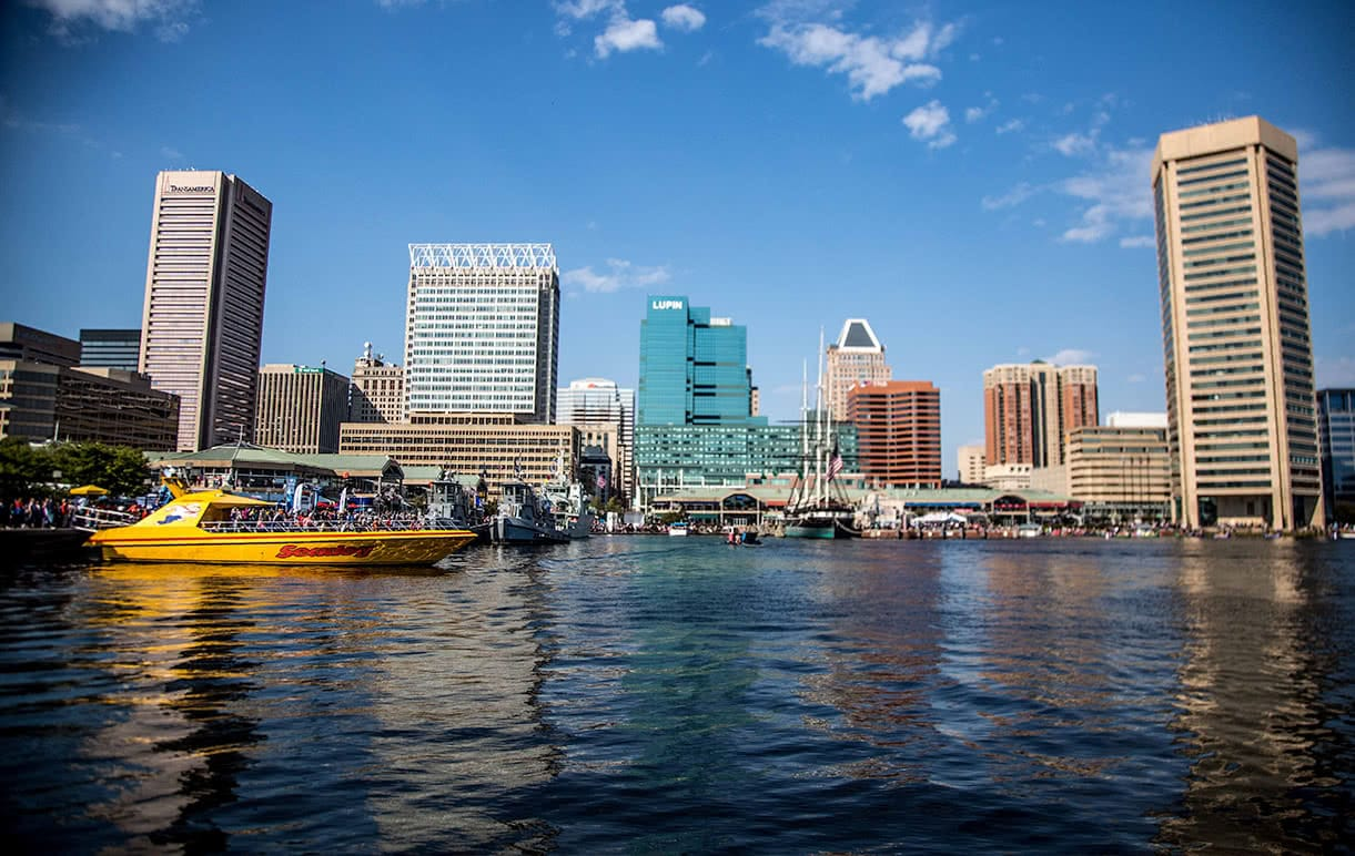A view of the Baltimore Inner Harbor from the water, showing boats and buildings