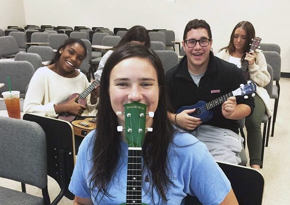 Students with ukuleles sitting in classroom chairs