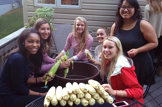 Students sitting around a table and shucking corn