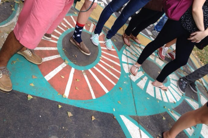 Students standing on and looking at a mural on the ground