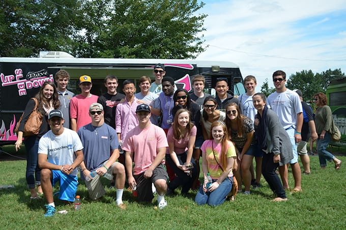 A large group of students posing for a photo in front of a food truck