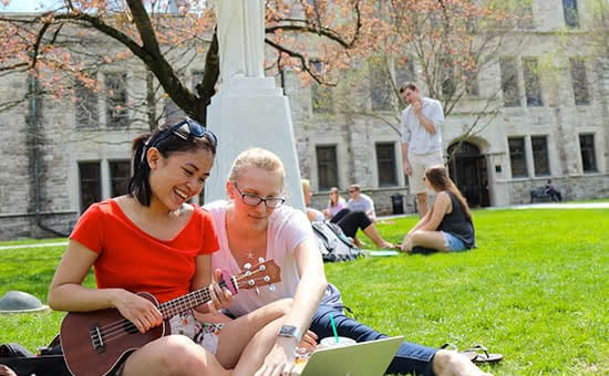 Students hanging out on the quad, one of them playing a ukelele
