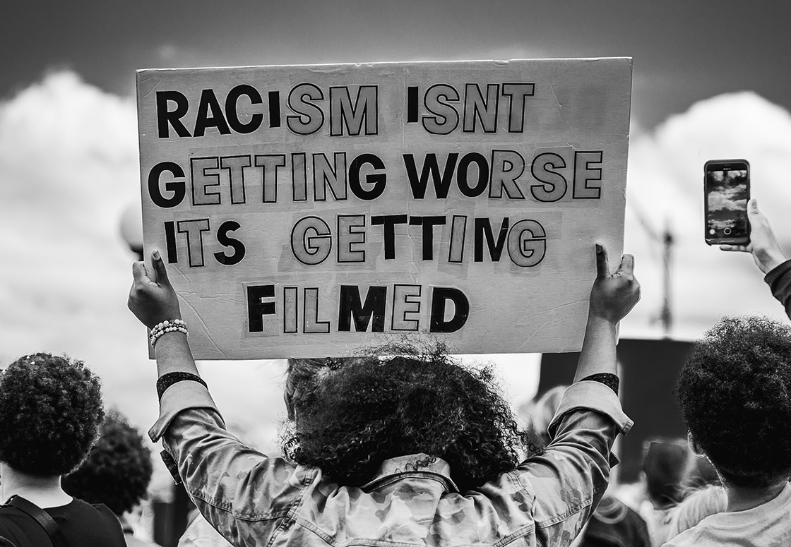 A protestor holding a sign that reads: Racism isn't getting worse, it's getting filmed