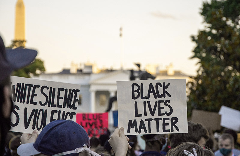 Handwritten signs being held up reading 'BLACK LIVES MATTER' and 'WHITE SILENCE IS VIOLENCE' at a protest
