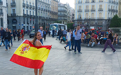 A student poses with the flag of Spain in Alcalá, Spain