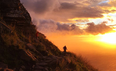 A person walks down the side of a mountain during sunset in Cape Town, South Africa