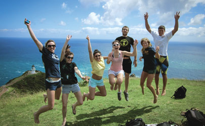 Students jumping in midair posing for a photo on a grassy hill by the ocean