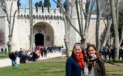Two students pose for a photo in front of a castle in Belgium