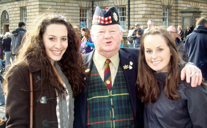 Students posing with a man dressed in traditional Scottish attire