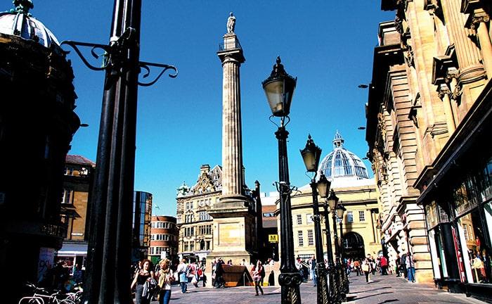 People walking past lampposts on the stone walkways of Newcastle, England