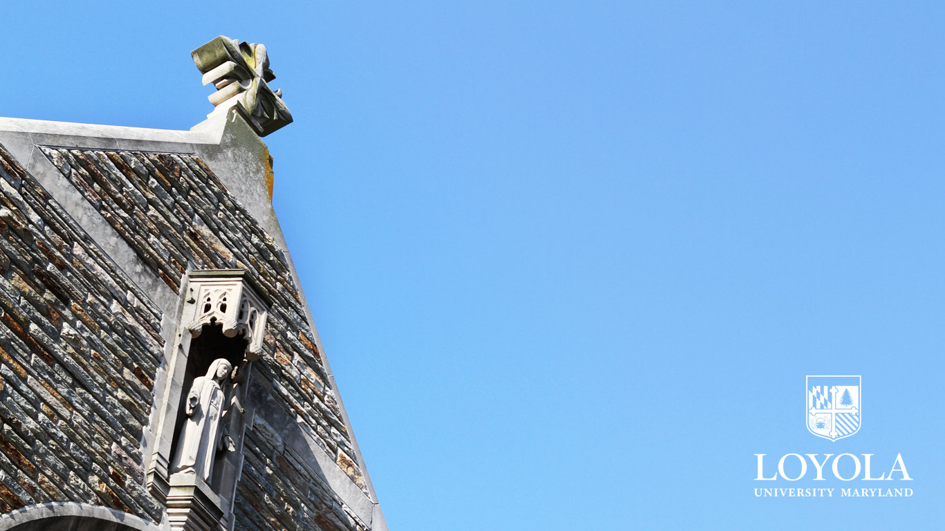 Angled photo of the top of the Alumni Memorial Chapel in front of a bright, blue sky