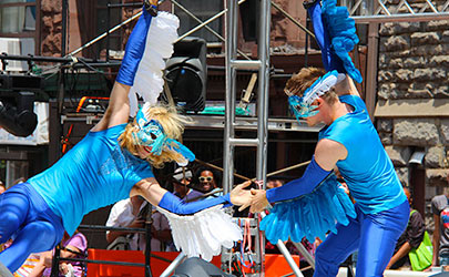 Dancers dressed in bright blue costumes with bird masks performing outdoors