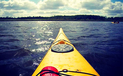 View from a yellow kayak in the water at a bright and cloudy day in the Chesapeake Bay